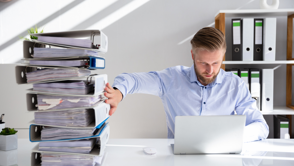 Man at desk pushing away paper document and switching to digital documents on a laptop